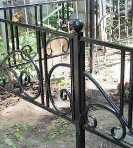 Кованые оградки на кладбище, кресты